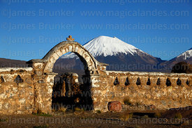 Stone arch entrance to rustic church near Lagunas and Parinacota volcano, Sajama National Park, Bolivia