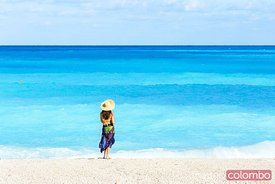 Woman with straw hat on famous Myrtos beach. Kefalonia, Greek Islands, Greece