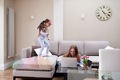 Little girl wearing sunglasses jumping on sofa while her mother working on laptop at coffee table
