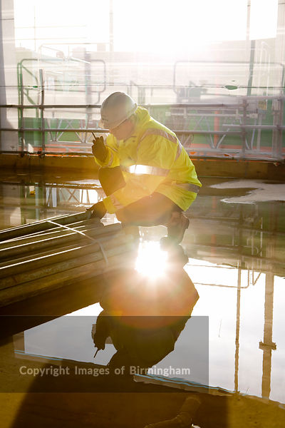 Construction site worker on a walkie talkie radio