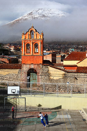 Boys playing basketball, San Sebastian church and snow covered Cerro Rico in background, Potosí, Bolivia