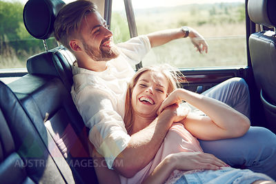 Happy young couple relaxing in car