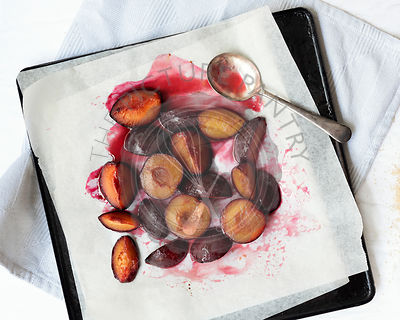 Roasted red plums in syrup with a spoon on a baking tray.