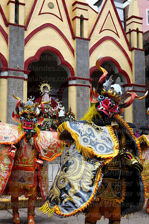Diablada devil dancers passing statue of Virgen de la Candelaria in entrance of her Sanctuary, Puno, Peru