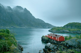 Red timber house by fjord