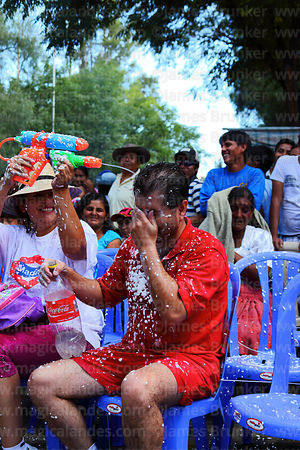 Woman squirts water over man sitting next to her with water pistol at carnival, Tarija, Bolivia