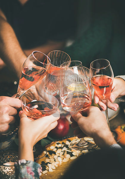 Friends clinking glasses with rose wine at Christmas table
