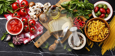 Italian food ingredients with Olives, pasta Spaghetti, Oil, Parmesan cheese, Brown mushroom, Tomato, Garlic, Basil, Chilli pepper and spices on dark marble background