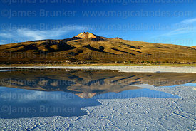 Tunupa volcano reflected in saline pool, Salar de Uyuni, Bolivia