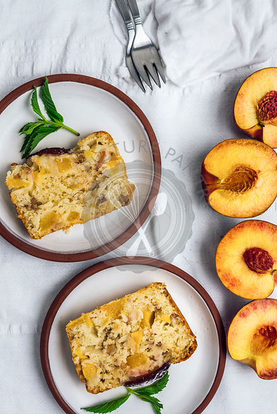 Peach bread served on two white plates on a white background accompanied by halved peaches photographed from top view.