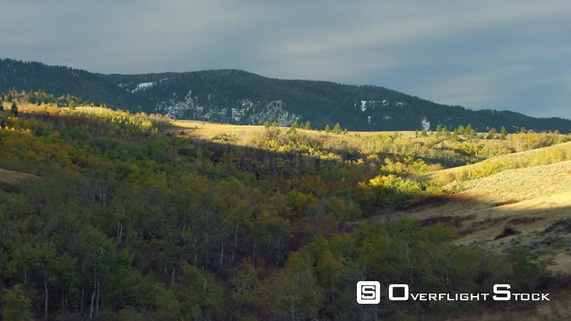 Bright yellow, gold and orang autumn colors dot the foothills of the Spanish Peaks near Bozeman, Montana