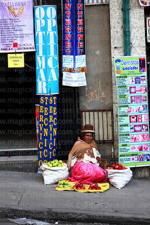 Aymara woman selling apples outside shopping centre, La Paz, Bolivia
