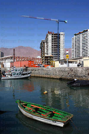 Rowing boat in port , building under construction in background , Iquique , Region I , Chile