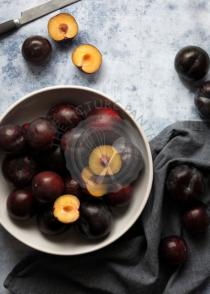 Cut and whole red plums in a bowl with a knife.