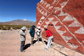 Tourists with guide visiting one of the coloured chulpas in Rio Lauca valley, Poquintica volcano in background, Bolivia