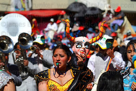 China Supay / female devil diablada dancer holding up her mask during the Gran Poder festival, La Paz, Bolivia