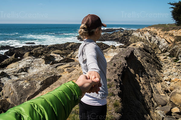 Close-up of a man holding his girlfriend's hand at beach