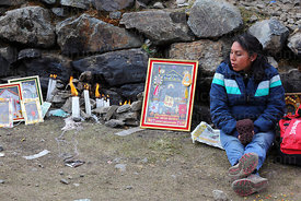 Devotee with candles and Señor de Qoyllur Riti picture outside Sanctuary, Qoyllur Riti festival, Peru