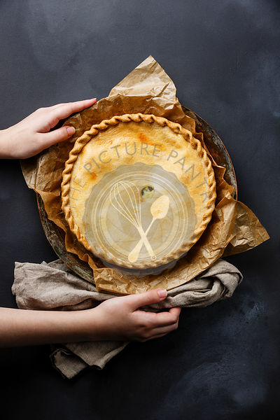 Cheese Pie with herbs and female hands on dark background