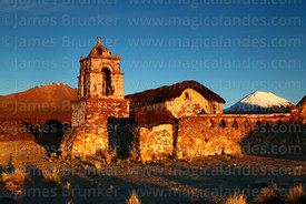 Rustic church near Lagunas just after sunrise, Parinacota volcano behind, Sajama National Park, Bolivia