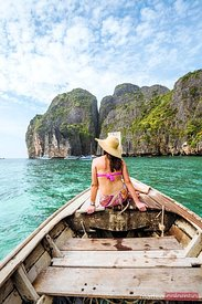 Woman with hat sitting on long tail boat, Thailand