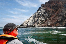 Tourist looking at rocky coastline on boat trip south of Arica, Region XV, Chile