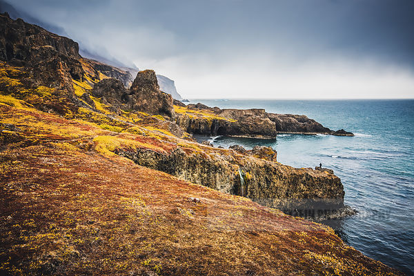 Dramatic coastline of Disko Island with autumn vegetation and waterfalls