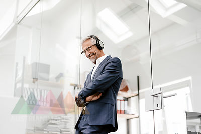 Happy mature businessman in office wearing headphones