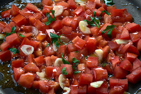 Chopped tomatoes in frying pan.