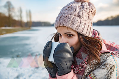 Woman drinking hot beverage from a cup outdoors in winter