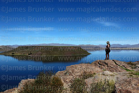 Tourist looking at view over Lake Umayo, Sillustani, Peru