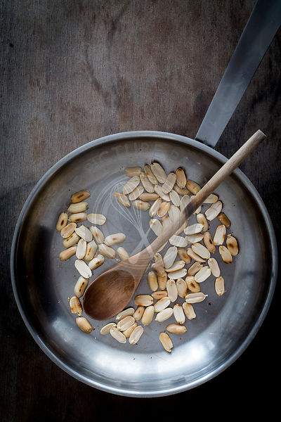 Roasted peanuts in steel skillet with wooden spatula on wooden tabletop. Top view