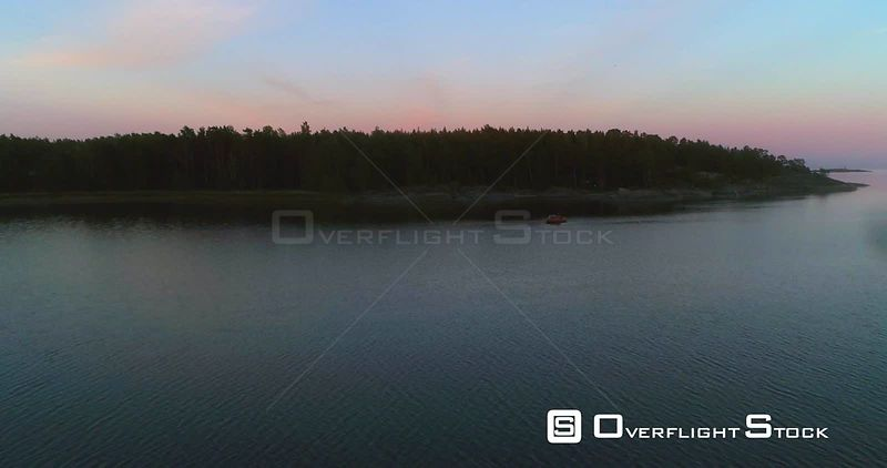 Boat at the coast, aerial view towards a yacht at the clear low waters of the baltic sea, on a sunny summer evening dusk, in Hanko, Finland