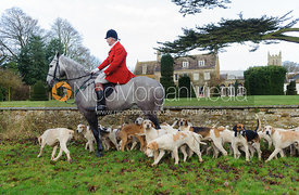 Master and Huntsman Andrew Osborne MFH with hounds in front of Pickwell Manor