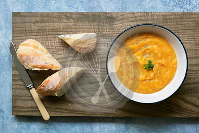 A bowl of homemade pumpkin soup on a wooden cutting board with a knife and three pieces of crusty bread.