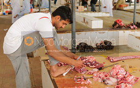 An arab man holds a butcher's knife with his foot, Salalah, Oman