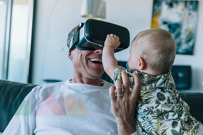 Happy man with baby wearing VR glasses