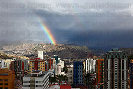 Rainbow over Sopocachi district and Muela del Diablo (a prominent rock outcrop overlooking the city) in rainy season , La Paz , Bolivia