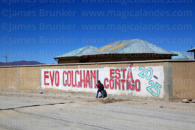 Schoolgirl walking past propaganda showing support for Evo Morales outside school in Colchani, Bolivia
