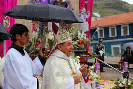 Assistant holding umbrella above bishop of Puno Jorge Carrion Pablisch during central mass, Virgen de la Candelaria festival, Puno, Peru