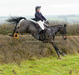 Meghan Healy jumping a hedge at Wilson's - The Cottesmore Hunt at Manor Farm
