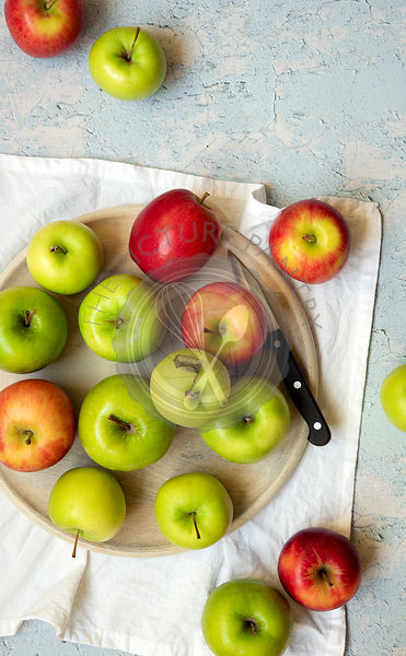 Red and green apples with a knife on a wooden serving board and a white napkin.
