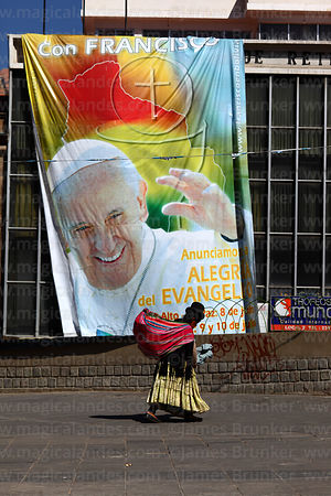 Aymara woman walking past banner for visit of Pope Francis, Plaza San Francisco, La Paz, Bolivia