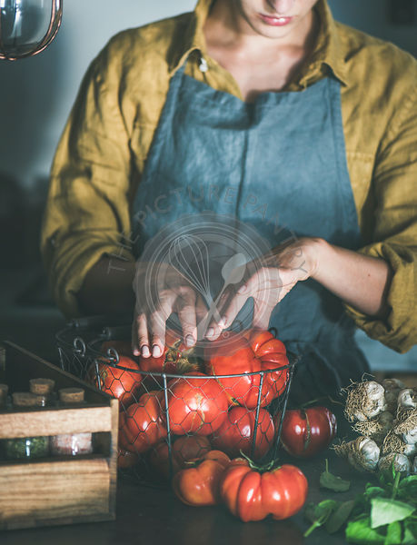 Woman in linen apron taking tomatoes out of basket