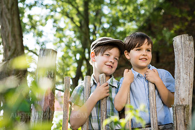 Portrait of two little boys standing behind a wooden fence