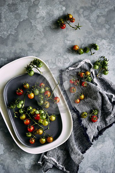 green cherry tomatos on grey and white plate.