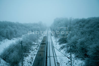 An atmospheric image of a frozon snow and Ice covered landscape with a train speeding along the tracks into the distance, in Northamptonshire, England.