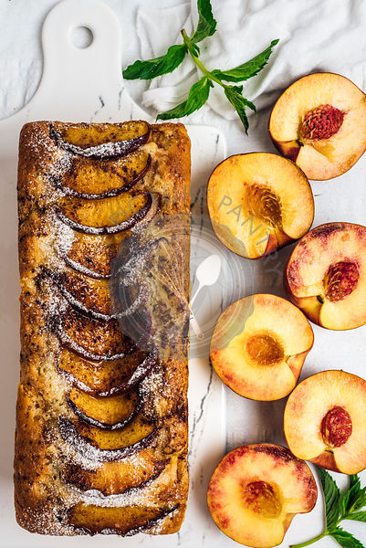A whole peach bread topped with cinnamon and brown sugar on white marble board photographed from top view. Accompanied by halved peaches.