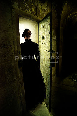 A semi-silhouette of a mystery Victorian woman walking into the cell of a decaying workhouse or prison.