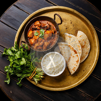 Chicken tikka masala spicy curry meat food with rice and naan bread on copper tray on wooden background
